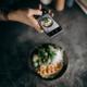 femme prenant une photo d'un plat avec un smartphone